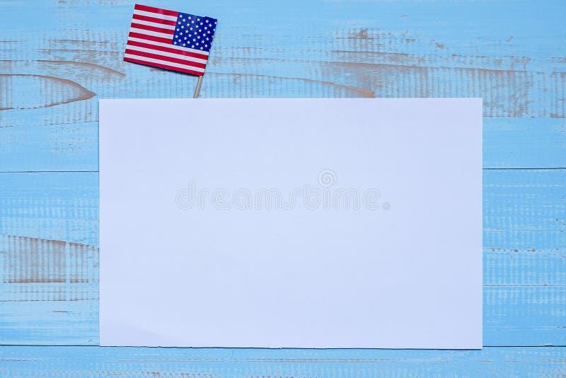 Κενή σημείωση εγγράφου με τη σημαία των Ηνωμένων Πολιτειών της Αμερικής στο μπλε ξύλινο υπόβαθρο ΑΜΕΡΙΚΑΝΙΚΕΣ διακοπές των παλαιμ στοκ εικόνα