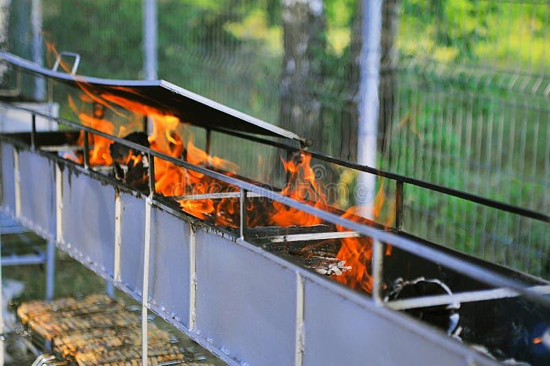 Κενή σχάρα ξυλάνθρακα σχαρών φλεμένος με τις φωτεινές φλόγες της πυρκαγιάς στοκ φωτογραφίες