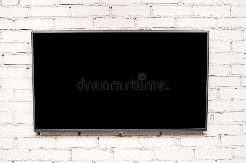 Κενή σύγχρονη επίπεδη TV οθόνης στον ελαφρύ τουβλότοιχο με το copyspa στοκ εικόνες με δικαίωμα ελεύθερης χρήσης