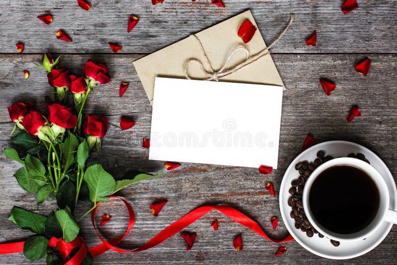 Κενοί άσπροι ευχετήρια κάρτα και φάκελος με το φλυτζάνι καφέ και τα κόκκινα τριαντάφυλλα στοκ εικόνες