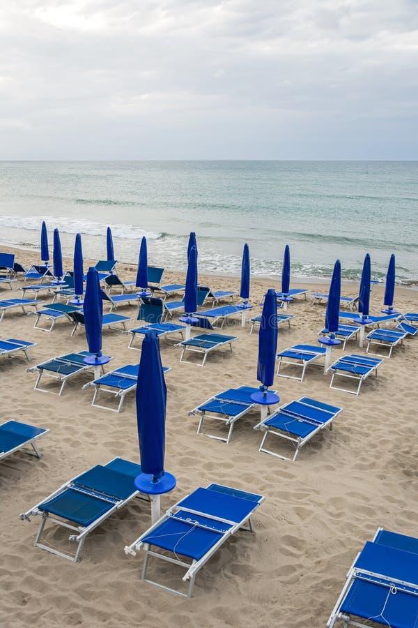 Κενοί αργόσχολοι παραλιών στην εγκαταλειμμένη παραλία στη χαμηλή εποχή στοκ φωτογραφία με δικαίωμα ελεύθερης χρήσης