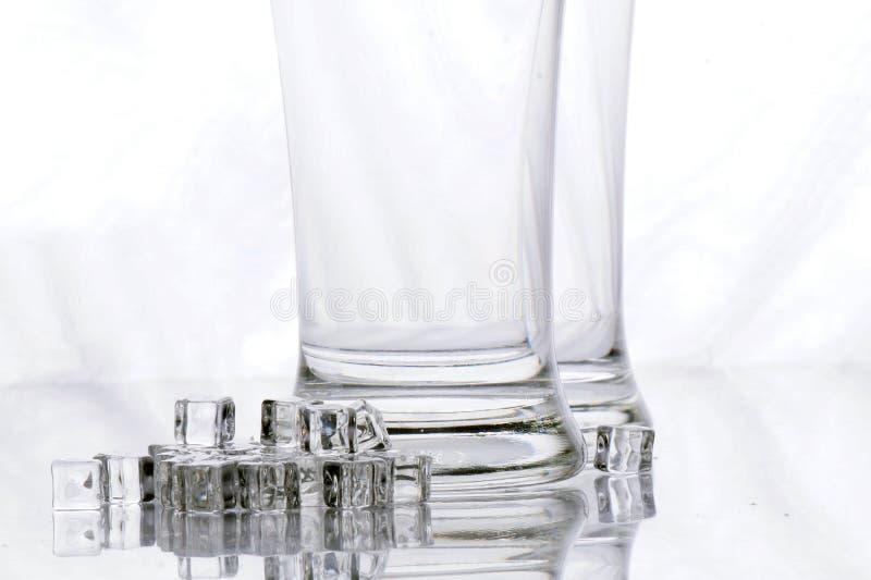Κενοί γυαλιά μπύρας και κύβοι πάγου στοκ εικόνες