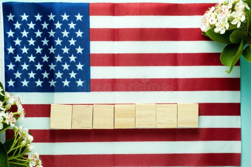Κενοί επτά ξύλινοι κύβοι που σχεδιάζονται κλάδους αμερικανικών σημαιών στους ανθίζοντας πλησίον στοκ φωτογραφία με δικαίωμα ελεύθερης χρήσης