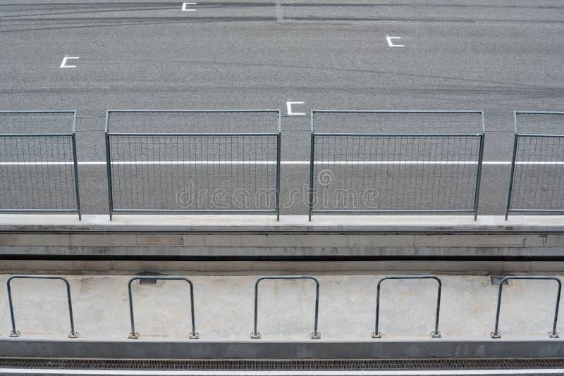 Κενοί οδικό κύκλωμα ασφάλτου και φράκτης ασφάλειας με την ΑΠΟΨΗ θέσης έναρξης ΑΠΟ την εξέδρα επισήμων στοκ εικόνες