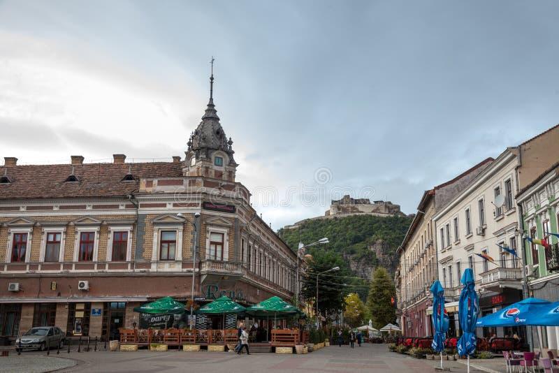 Κεντρικός δρόμος της πόλης Transylvanian Deva Το κάστρο της πόλης, σε έναν λόφο, μπορεί να δει στο υπόβαθρο στοκ εικόνες