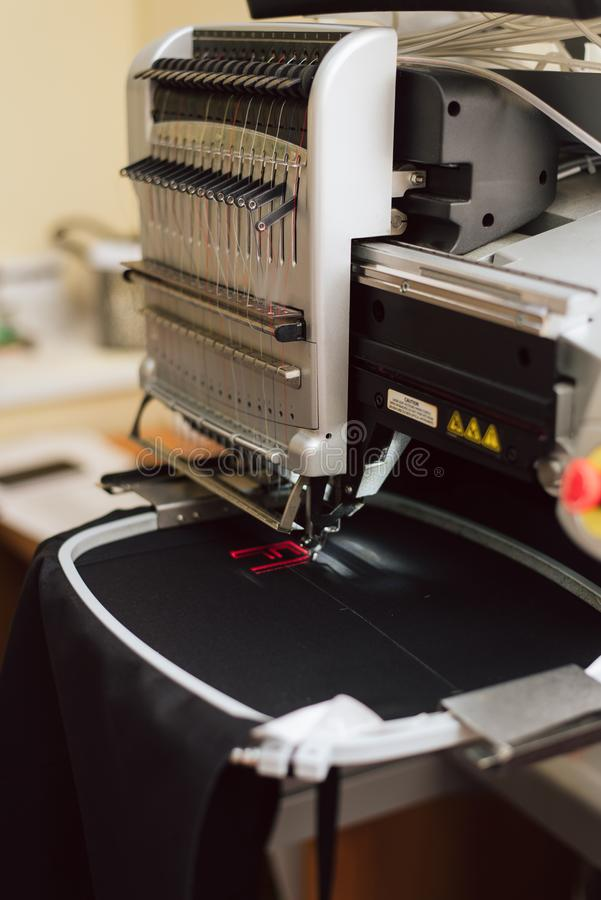 Κεντώντας κείμενο σε μια ράβοντας μηχανή σε μια βιομηχανική κλίμακα η μηχανή κεντά το γράμμα φ στο ύφασμα στοκ εικόνα