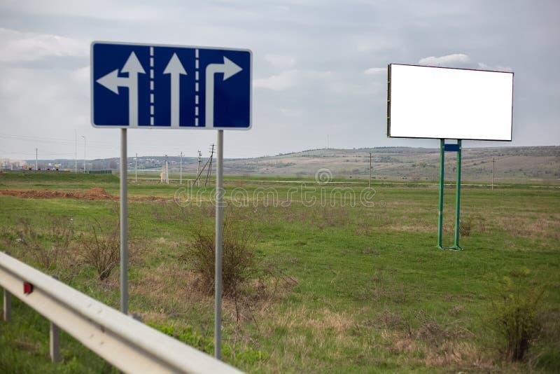 Κενός άσπρος πίνακας διαφημίσεων με το πρότυπο για τα σημάδια διαφήμισης και δρόμων στον πράσινο τομέα στοκ φωτογραφία με δικαίωμα ελεύθερης χρήσης