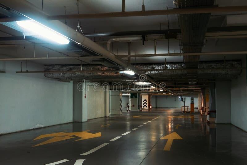 Κενός διάδρομος στο φωτισμένο υπόγειο εσωτερικό χώρων στάθμευσης αυτοκινήτων κάτω από τη σύγχρονη λεωφόρο με τα βέλη στο πάτωμα στοκ εικόνα