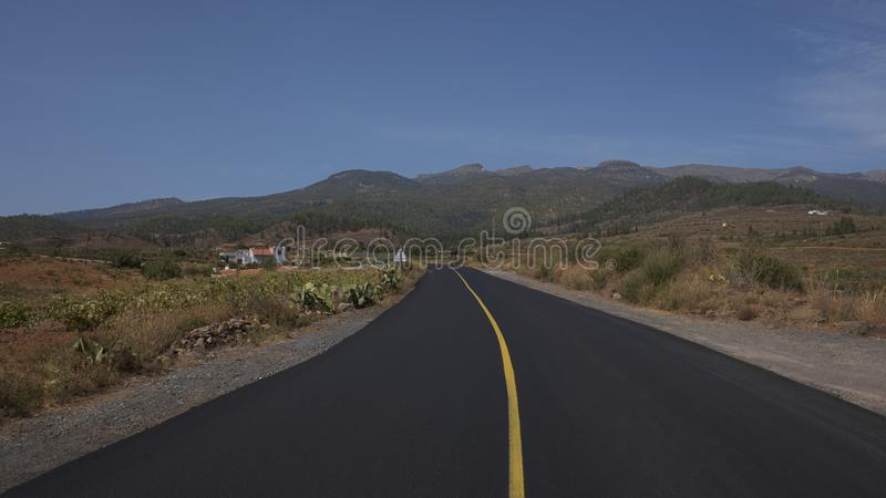 Κενός δρόμος Arona του δήμου, που περιβάλλονται μέσω από τους αμπελώνες, των terraced αγροκτημάτων και της άγριας ενδημικής χλωρί στοκ εικόνα με δικαίωμα ελεύθερης χρήσης