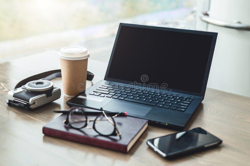 κενός εργασιακός χώρος Κοντά στο παράθυρο στο γραφείο είναι lap-top, smartphone, σημειωματάριο, γυαλιά, φλιτζάνι του καφέ, κάμερα στοκ εικόνες