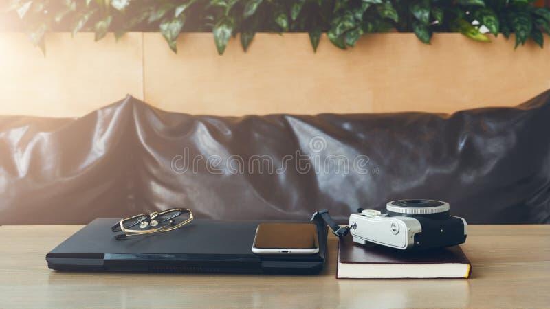 Κενός εργασιακός χώρος στον καφέ χωρίς ανθρώπους Στο lap-top γραφείων, smartphone, σημειωματάριο εγγράφου, γυαλιά, κάμερα για τις στοκ εικόνες