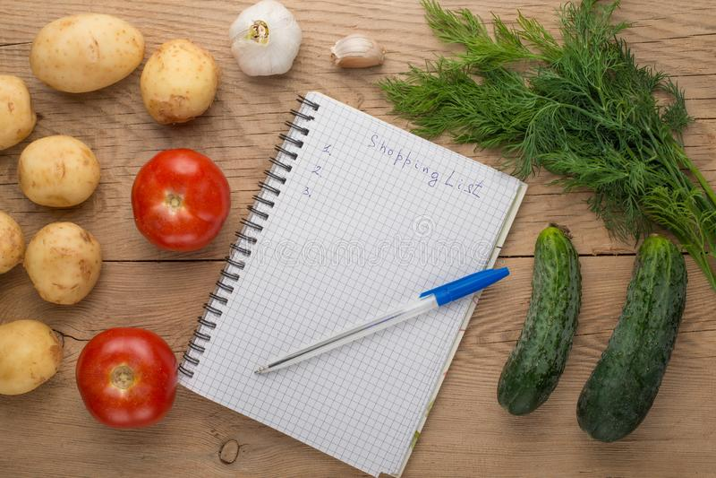 Κενός κατάλογος αγορών σχετικά με χαρτί με τα λαχανικά στον ξύλινο πίνακα στοκ εικόνες