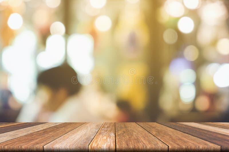 Κενός ξύλινος πίνακας καφετιού στο μπροστινό θολωμένο ζωηρόχρωμο υπόβαθρο, για την παρουσίαση και το προϊόν και το πρότυπο διαφήμ στοκ φωτογραφία