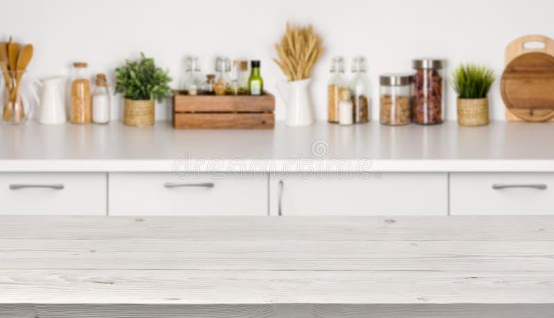 Κενός ξύλινος πίνακας με την εικόνα bokeh του εσωτερικού πάγκων κουζινών στοκ εικόνες