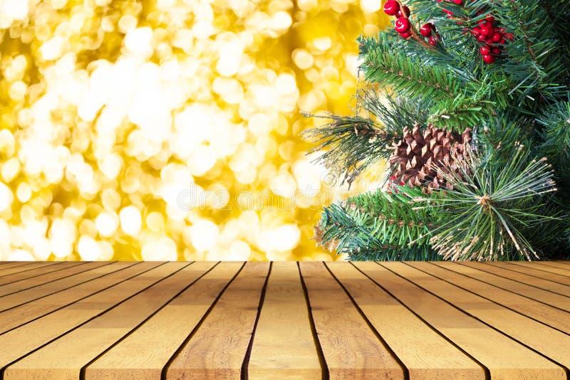 Κενός ξύλινος πίνακας προοπτικής μπροστά από το χριστουγεννιάτικο δέντρο και το χρυσό υπόβαθρο bokeh, για το montage επίδειξης πρ στοκ εικόνες