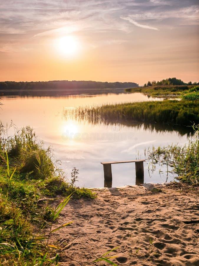 Κενός πάγκος κοντά στον ποταμό στο ηλιοβασίλεμα Μακρυά από την επίσπευση και το μαξιλαράκι Ήλιος που θέτει πέρα από τον ορίζοντα  στοκ φωτογραφίες