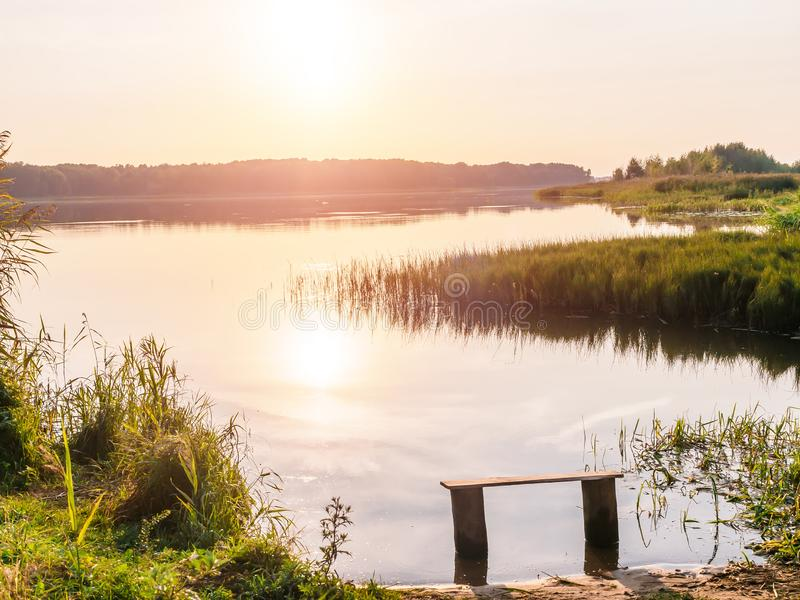 Κενός πάγκος κοντά στον ποταμό στο ηλιοβασίλεμα Μακρυά από την επίσπευση και το μαξιλαράκι Ήλιος που θέτει πέρα από τον ορίζοντα  στοκ φωτογραφία
