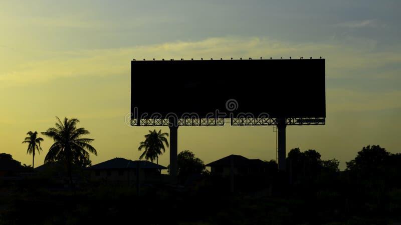 Κενός πίνακας διαφημίσεων σκιαγραφιών με τον ουρανό στο ηλιοβασίλεμα στοκ φωτογραφία με δικαίωμα ελεύθερης χρήσης