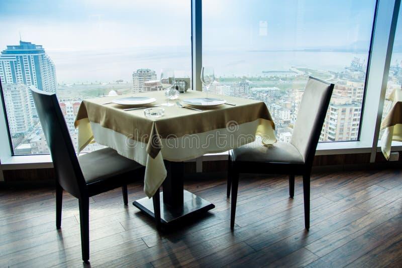 Κενός πίνακας εστιατορίων για δύο με τη μεγάλη άποψη παραθύρων στοκ εικόνες με δικαίωμα ελεύθερης χρήσης