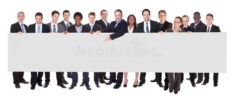 Κενός πίνακας διαφημίσεων εκμετάλλευσης Multiethnic businesspeople στοκ εικόνα με δικαίωμα ελεύθερης χρήσης