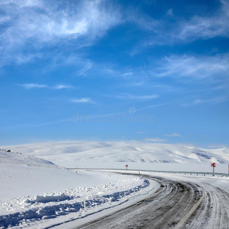 Κενός παγωμένος δρόμος ασφάλτου και χιονισμένο τοπίο με το mounta στοκ εικόνα με δικαίωμα ελεύθερης χρήσης