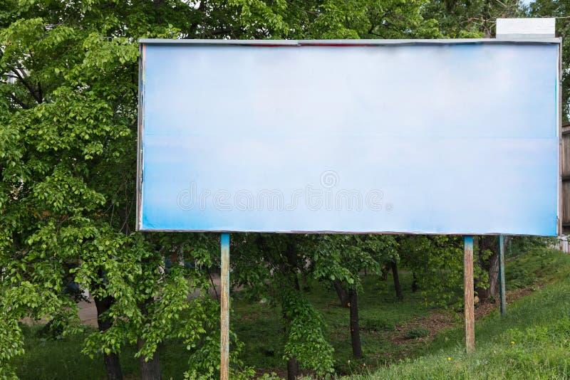 Κενός παλαιός πίνακας διαφημίσεων στο πράσινο υπόβαθρο - για τη νέα διαφήμιση στοκ εικόνες με δικαίωμα ελεύθερης χρήσης