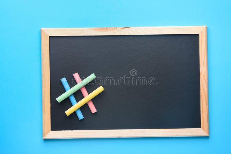 Κενός πλαστός επάνω μαύρος πίνακας κιμωλίας με το σημάδι Hashtag που γίνεται από το πολύχρωμο μπλε υπόβαθρο κιμωλιών Πίσω στην εκ στοκ φωτογραφίες