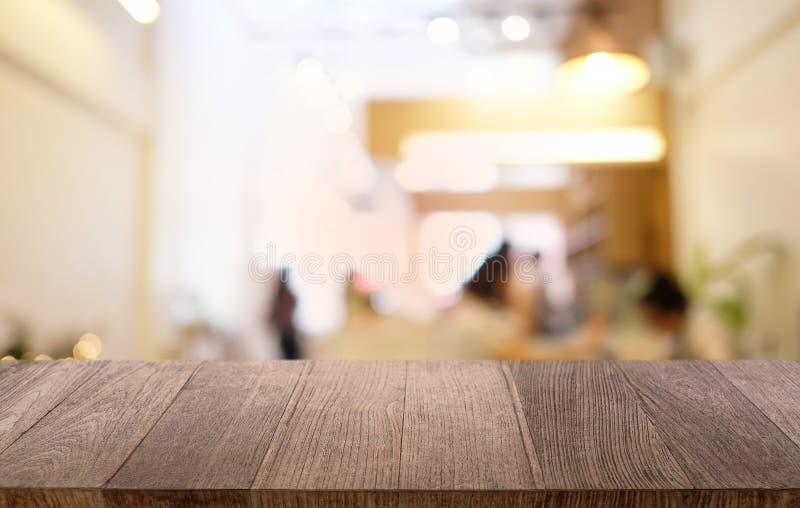 Κενός σκοτεινός ξύλινος πίνακας μπροστά από θολωμένο το περίληψη bokeh υπόβαθρο του εστιατορίου μπορέστε να χρησιμοποιηθείτε για  στοκ εικόνες