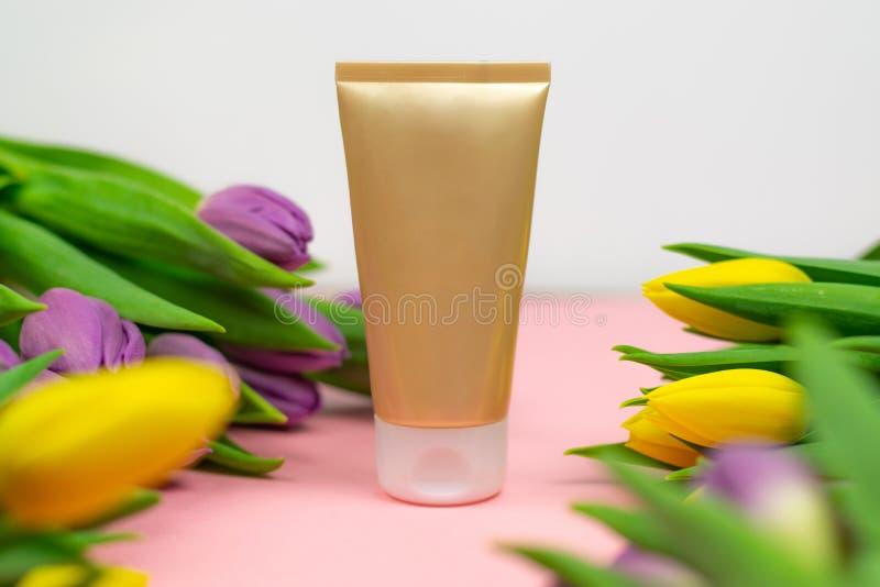 Κενός σωλήνας της κρέμας σε ένα ρόδινο υπόβαθρο με τα λουλούδια στοκ εικόνα με δικαίωμα ελεύθερης χρήσης