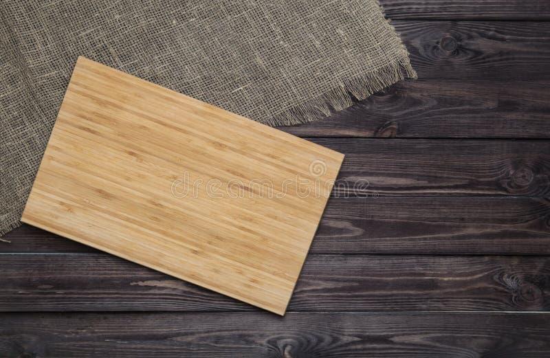 Κενός τέμνων πίνακας στη σκοτεινή ξύλινη έννοια υποβάθρου τροφίμων σανίδων στοκ φωτογραφία με δικαίωμα ελεύθερης χρήσης
