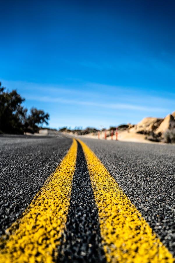 Κενός φυσικός μακρύς ευθύς δρόμος ερήμων με τις κίτρινες γραμμές χαρακτηρισμού Καλιφόρνια στοκ εικόνα