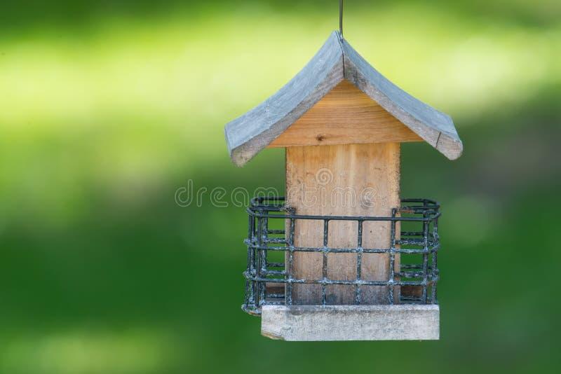Κενός χρησιμοποιημένος suet τροφοδότης πουλιών σπιτιών πουλιών στο κατώφλι με το πράσινο υπόβαθρο στοκ φωτογραφία με δικαίωμα ελεύθερης χρήσης