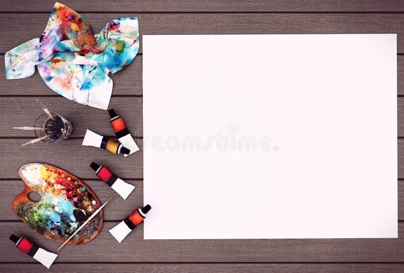 Κενό άσπρο έγγραφο αφισών με το διάστημα για τη χλεύη επάνω στο ξύλινο υπόβαθρο με τα χρώματα παλετών, πινέλων και χρωμάτων χρώμα διανυσματική απεικόνιση