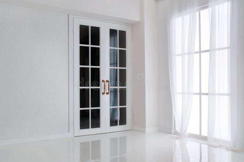 Κενό άσπρο δωμάτιο με τη μεγάλη γαλλική πόρτα παραθύρων και γυαλιού στοκ φωτογραφία με δικαίωμα ελεύθερης χρήσης