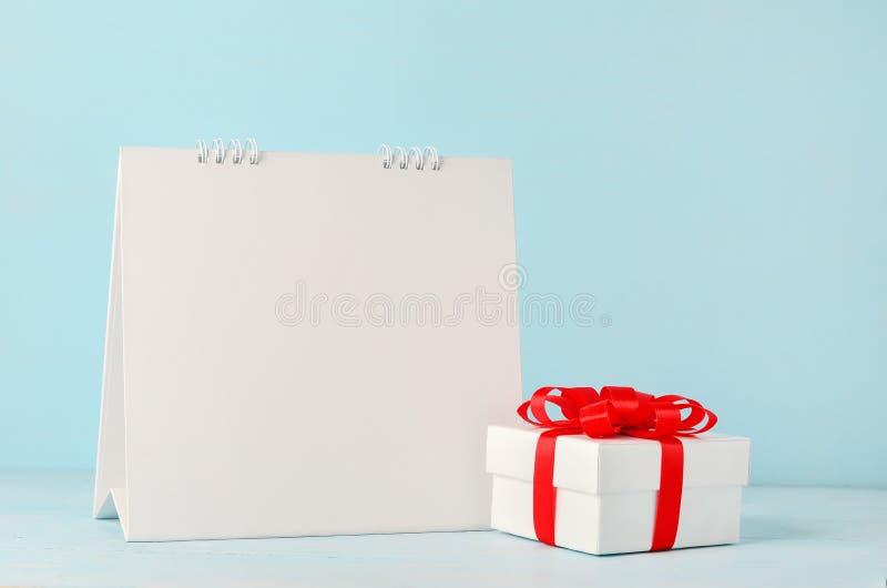 Κενό άσπρο ημερολόγιο γραφείων και κιβώτιο δώρων Χριστουγέννων με την κόκκινη κορδέλλα στοκ εικόνες με δικαίωμα ελεύθερης χρήσης