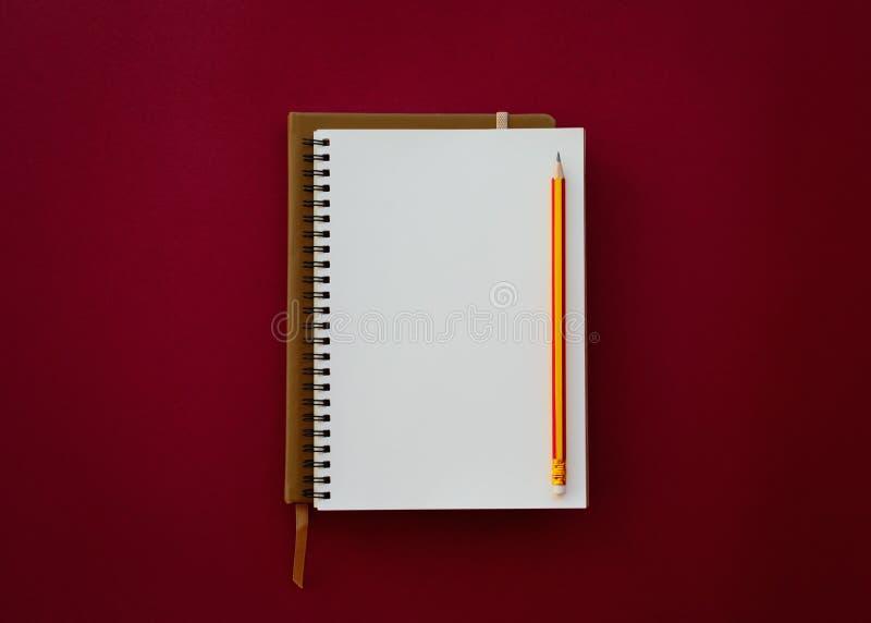 """Κενό άσπρο σημειωματάριο με Ï""""Î¿ μολύβι στο κόκκινο υπόβαθρο εγγράφου στοκ φωτογραφία"""