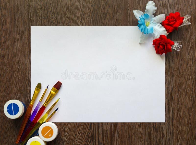 Κενό άσπρο φύλλο του εγγράφου για το κείμενό σας σε ένα σκοτεινό ξύλινο επιτραπέζιο υπόβαθρο Υπάρχουν χρωματισμένα χρώματα, βούρτ στοκ φωτογραφίες