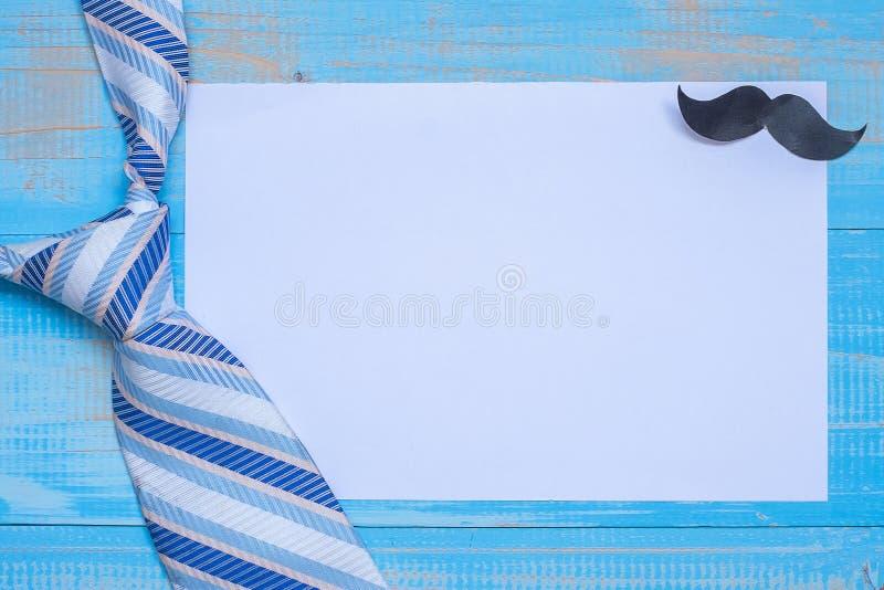 Κενό έγγραφο σημειώσεων με τις μπλε γραβάτες και mustache για το ξύλινο υπόβαθρο Έννοιες ημέρας του ευτυχούς πατέρα και ημέρας τω στοκ εικόνα