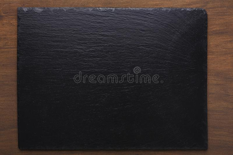 Κενό αγροτικό μαύρο πιάτο πετρών πλακών στο ξύλινο υπόβαθρο στοκ εικόνα