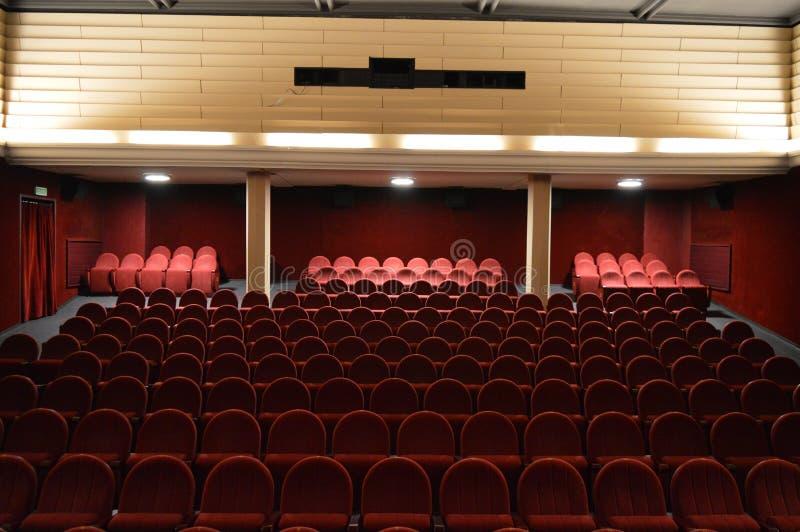 Κενό ακροατήριο κινηματογράφων με τα κόκκινα καθίσματα στοκ εικόνες