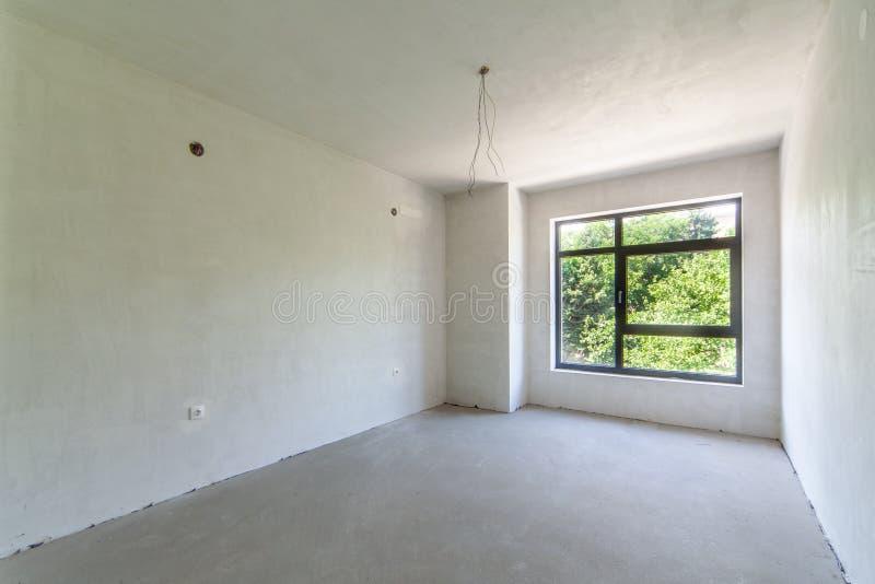 Κενό ατελές δωμάτιο Ατελές εσωτερικό, άσπρο δωμάτιο κτηρίου Επισκευές στο διαμέρισμα στοκ εικόνα