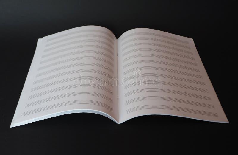 Κενό βιβλίο φύλλων μουσικής για το γράψιμο των σημειώσεων που απομονώνονται στο μαύρο υπόβαθρο στοκ φωτογραφίες