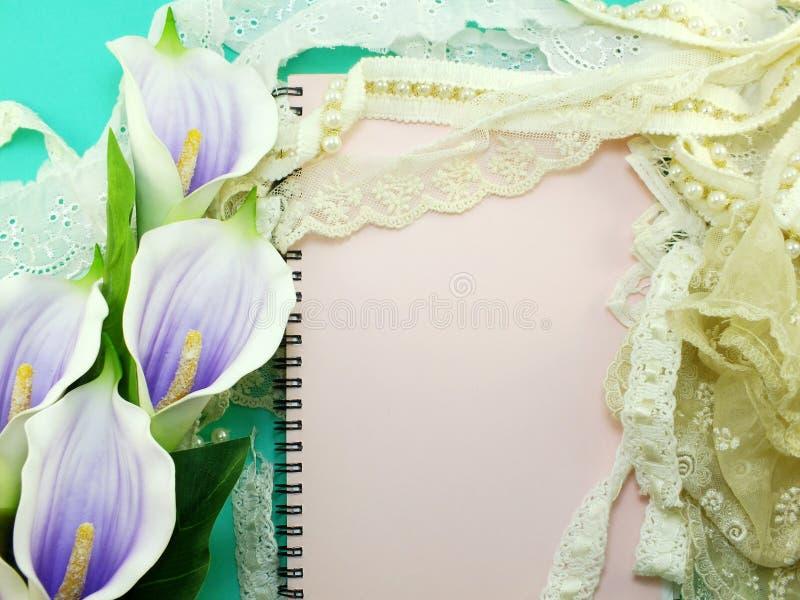 κενό βιβλίο σημειώσεων που ανοίγει με το ντεκόρ δαντελλών και το τεχνητό calla λουλούδι στοκ εικόνες
