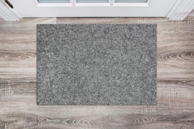 Κενό γκρίζο μάλλινο doormat πριν από την άσπρη πόρτα στην αίθουσα Χαλί στο ξύλινο πάτωμα, πρότυπο προϊόντων στοκ φωτογραφίες με δικαίωμα ελεύθερης χρήσης
