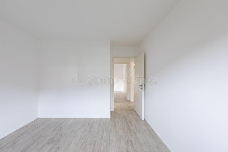 Κενό δωμάτιο με τους άσπρους τοίχους και ανοιχτή πόρτα στο δικαίωμα στοκ εικόνες