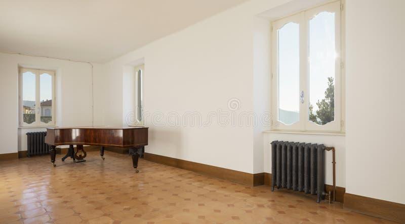 Κενό δωμάτιο με το παλαιό πιάνο και τις εκλεκτής ποιότητας θερμάστρες στοκ φωτογραφίες