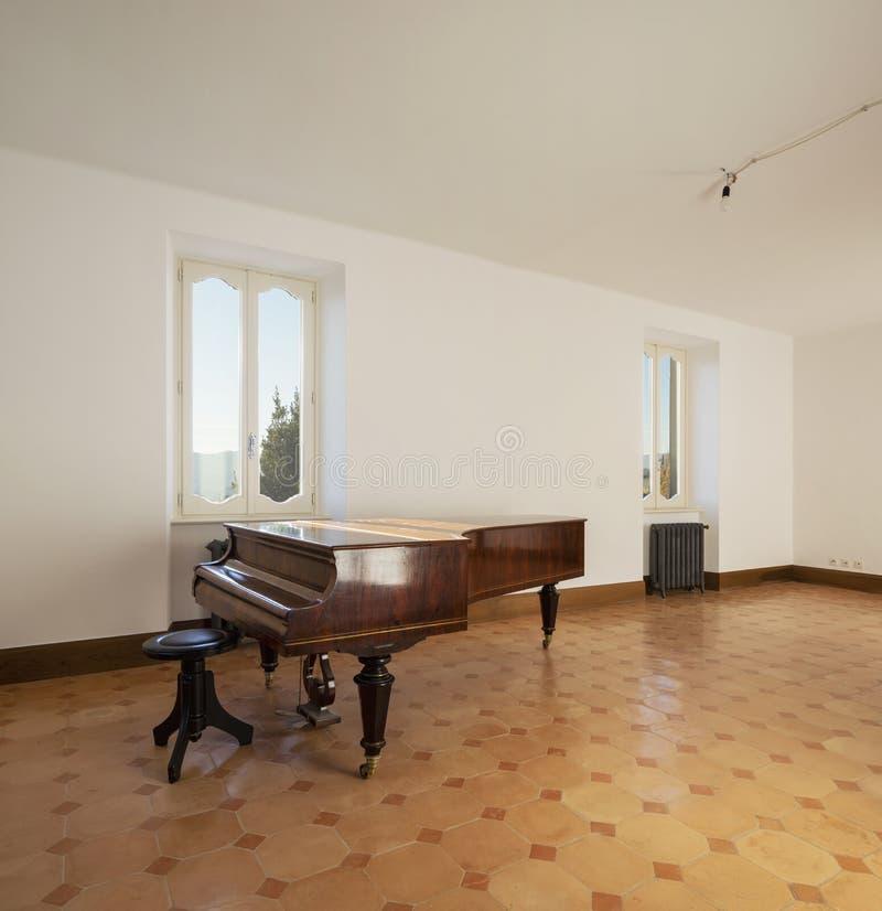 Κενό δωμάτιο με το παλαιό πιάνο και τις εκλεκτής ποιότητας θερμάστρες στοκ εικόνα με δικαίωμα ελεύθερης χρήσης