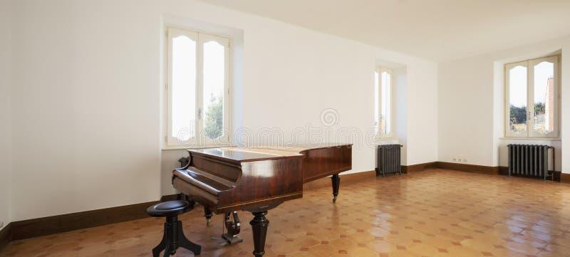 Κενό δωμάτιο με το παλαιό πιάνο και τις εκλεκτής ποιότητας θερμάστρες στοκ εικόνες με δικαίωμα ελεύθερης χρήσης