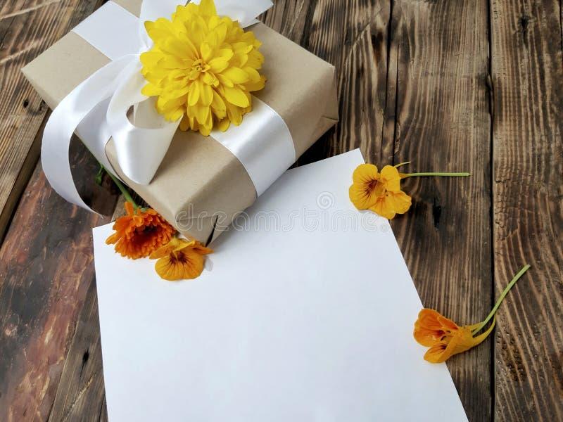 Κενό κενό εγγράφου με το δώρο και λουλούδια στο ξύλινο υπόβαθρο στοκ φωτογραφία με δικαίωμα ελεύθερης χρήσης