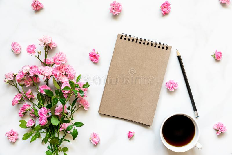 Κενό εκλεκτής ποιότητας σημειωματάριο εγγράφου στο πλαίσιο φιαγμένο από ρόδινα ροδαλά λουλούδια με το φλυτζάνι καφέ πέρα από τον  στοκ φωτογραφία